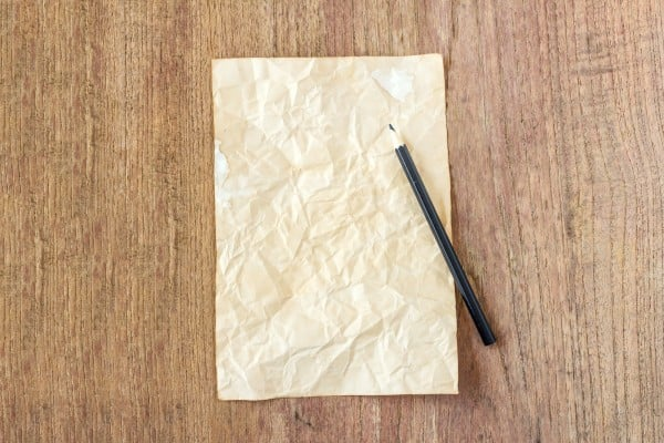 old paper with black pencil on wooden table
