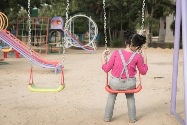 Lonely girl sitting on chain swing