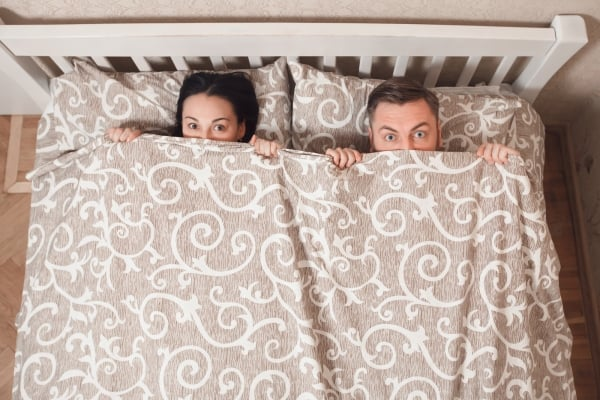 Young couple peeping from bedsheet at bedroom.