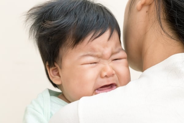 Adorable asian baby sick and crying on mom shoulder.