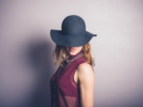 Seductive young woman in hat and transparent shirt