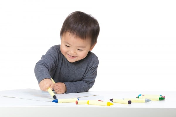 Asian boy drawing with crayon