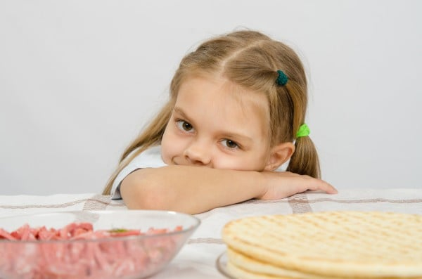 Little girl sitting at a table with his head on his hand with a smile and looking at the food in front of her